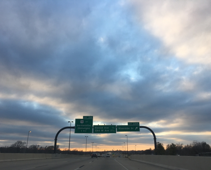 [Clouds with a sunset on the horizon, offset by a highway exit sign]